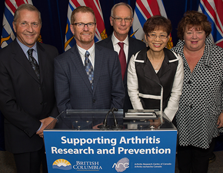 "Government of BC awards ARC $3 million for arthritis research. Left to right: Ron McKerrow, ARC Board Chair; Minister Terry Lake, Minister of Health; Dr. John Esdaile, Scientific Director ARC; Minister Teresa Wat, MLA Richmond Centre; Linda Reid, Speaker of the House & MLA, Richmond East. Sign they are standing behind says, ""Supporting Arthritis Research and Prevention""."